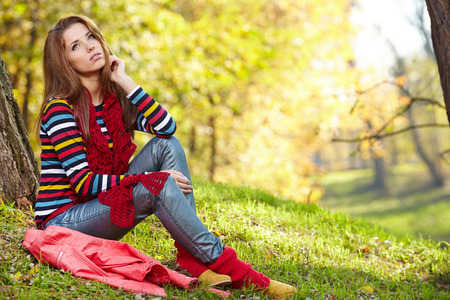 Fall woman relaxing happy in autumn forest foliage sitting photo