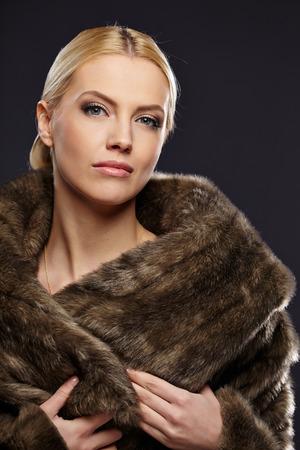 Woman in luxury fur coat. Vintage style. Brown background.  photo