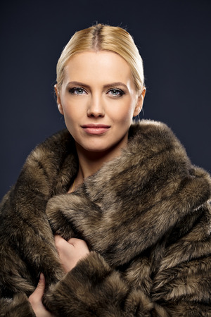 Woman in luxury fur coat. Vintage style. Brown background.  photo