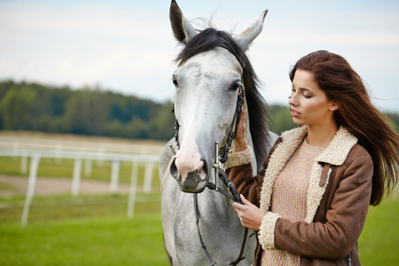 An attractive young woman with a horse  photo