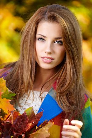 pelo castaño claro: Mujer hermosa en parque del otoño Foto de archivo