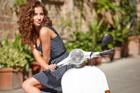 Young beautiful italian woman sitting on a italian scooter.  photo