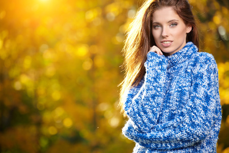Beautiful elegant woman standing in a park in autumn  photo