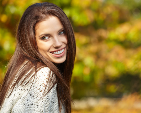 Beautiful fashion woman standing in a park in autumn  photo
