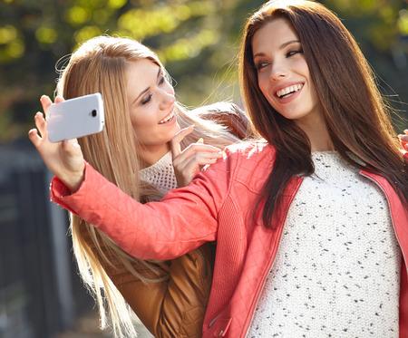 Friends making selfie. Two beautiful young women making selfie photo