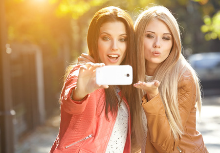 Friends making selfie. Two beautiful young women making selfie photo