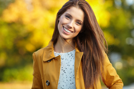 Beautiful elegant woman standing in a park in autumn Stock Photo