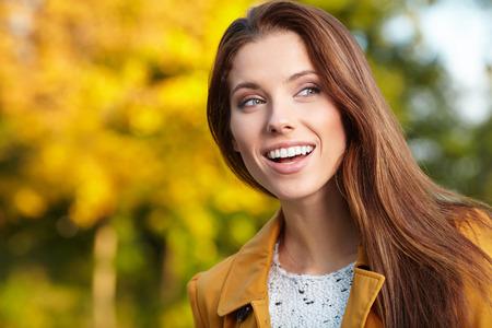 niñas sonriendo: Hermosa mujer elegante de pie en un parque en otoño