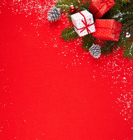 Gifts and Christmas tree branch in the snow and red background, top view photo