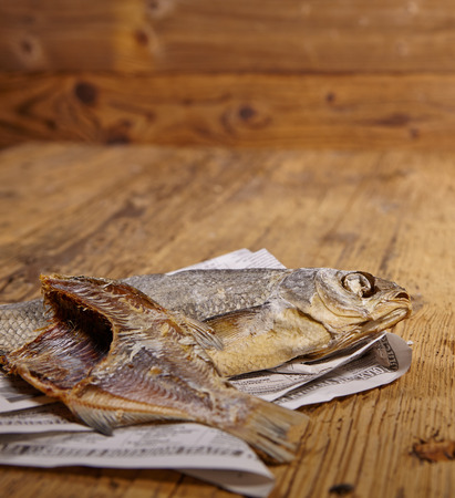 dried fish: Russian snack . Dried fish on old newspaper