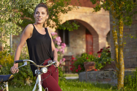 agriturismo: Woman with vintage bike  in Tuscany garden Stock Photo