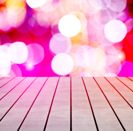 holiday lights display: Christmas holiday background with empty wooden deck table over festive bokeh.