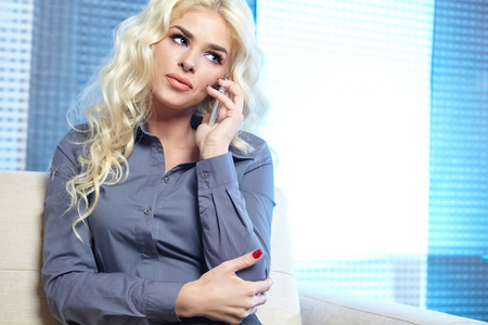 smile close up: Beautiful blonde  woman talking on mobile phone at home