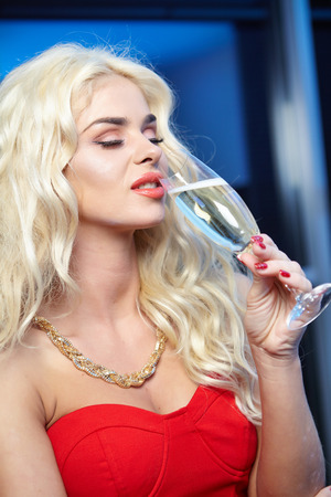 Happy and beautiful blond woman in a party red dress with a glass of champagne photo