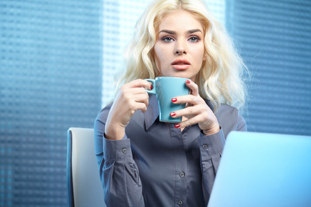 Blonde pretty business woman working at her office. She is very busy and hot. photo