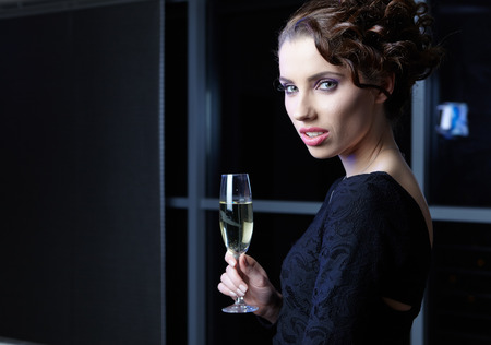Portrait of a very fashionable, cool and elegant festive woman with champagne photo