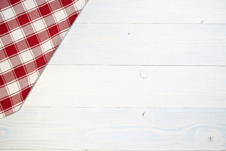bleached: red folded tablecloth over old wooden table Stock Photo