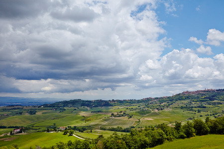 Scenic Tuscany landscape with rolling hills and beautiful cloudscape in Val dOrcia, Italy photo