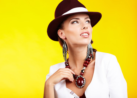 Fasionable woman in a hat over yellow background photo