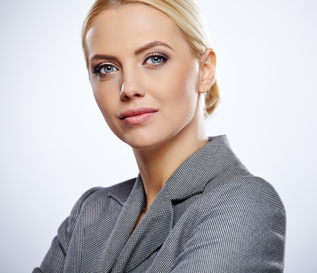 Portrait of a beautiful young business woman standing against blue  background photo