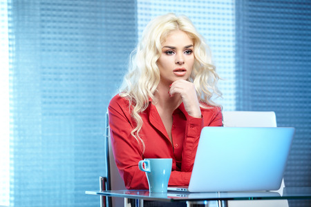 Adult young pretty business woman working at her office. photo