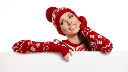 Winter girl happy smile hold sale poster, attractive young excited woman wear warm wool sweater red hat, blank board isolated over white background photo