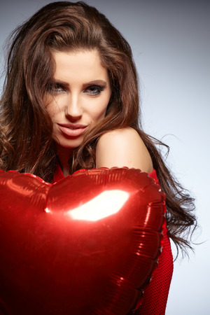 Beautiful brunette young woman in red with a heart-shaped balloons photo