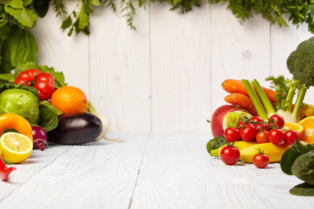 frame with fresh organic vegetables and fruits on wooden background