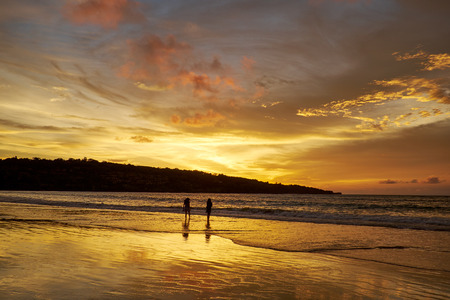 silhouettes of couples on the beach in sunset photo