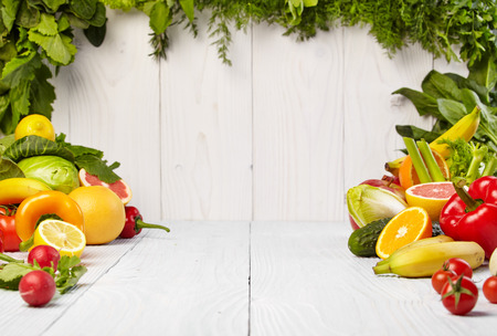 and organic: frame with fresh organic vegetables and fruits on wooden background