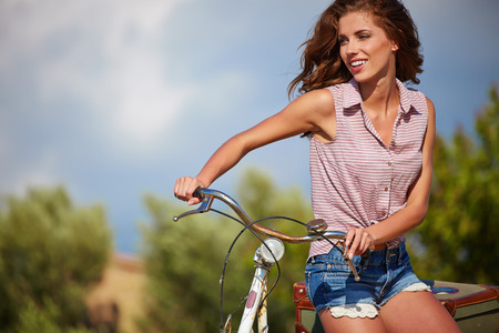 Sexy woman with vintage bike in a country road. photo
