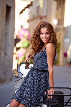 Italienische Frau auf einem Roller auf den Straßen von der toskanischen Stadt. Lizenzfreie Bilder