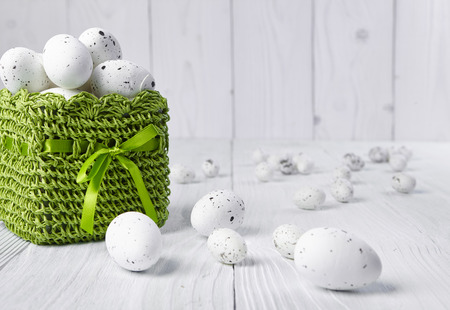 speckled wood: Easter eggs in a green basket on a white table Stock Photo