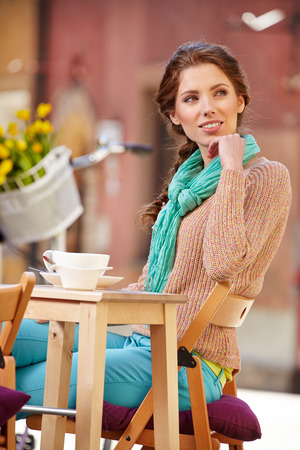 beautiful young girl drinking coffee in a old town cafe - outdoor portrait photo