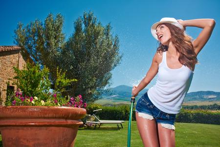 Beautiful young woman having fun in summer garden with garden hose splashing summer rain. photo