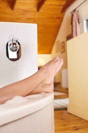bubble bath: Bathtime. Girls feet sticking out from bath tub.
