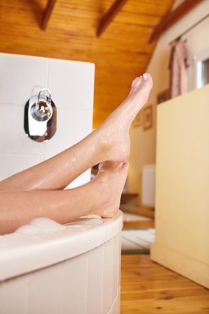 feet washing: Bathtime. Girls feet sticking out from bath tub.