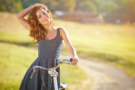 road cycling: Sexy woman with vintage bike in a country road. Stock Photo