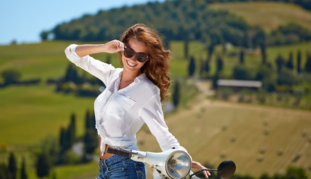 cuntry: Young beautiful italian woman sitting on a italian scooter in tuscany outdoor