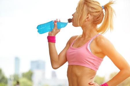 or thirsty: Mujer deportiva Thirsty agua potable despu�s del entrenamiento Foto de archivo