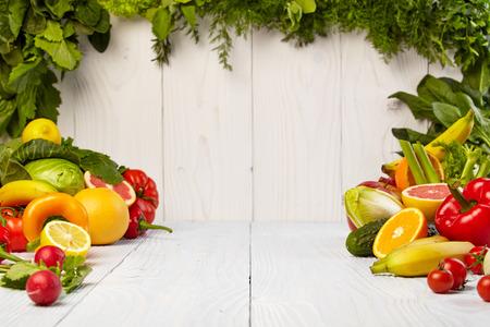 frutas: Frutas y verduras Frutas y limita con las fronteras de verduras en la mesa de madera Foto de archivo