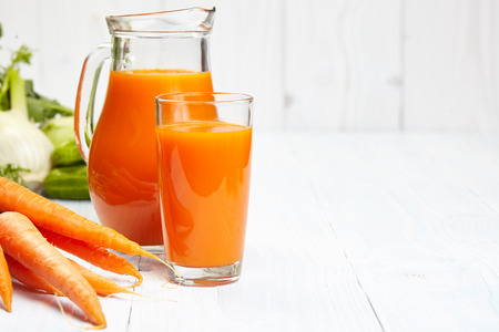 juice fresh vegetables: carrot juice on white wood  background