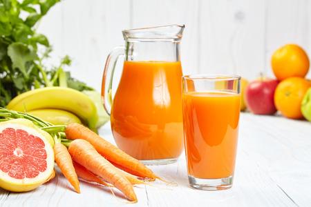 heathy diet: carrot juice on white wood  background