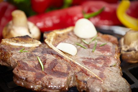 sizzling: T-bone steak on the barbecue grill with vegetable spears in the background