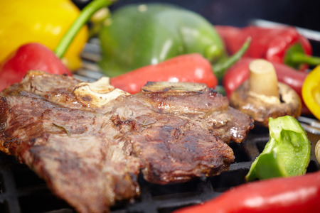 mouth watering: T-bone steak on the barbecue grill with vegetable spears in the background