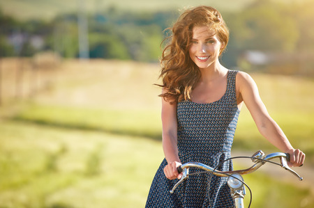 country girl: Sexy woman with vintage bike in a country road. Stock Photo