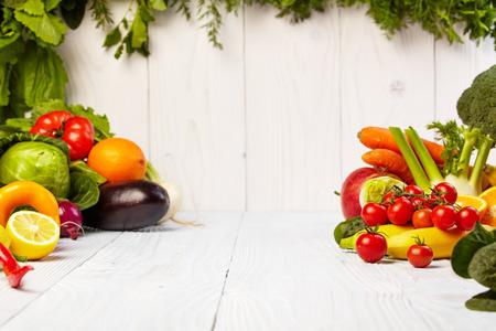 comiendo fruta: Frutas y verduras Frutas y limita con las fronteras de verduras en la mesa de madera Foto de archivo