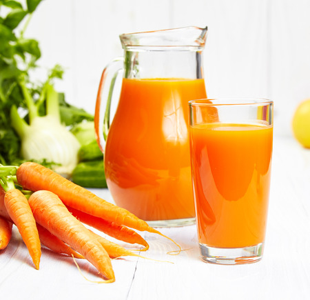 carrot juice on white wood table photo