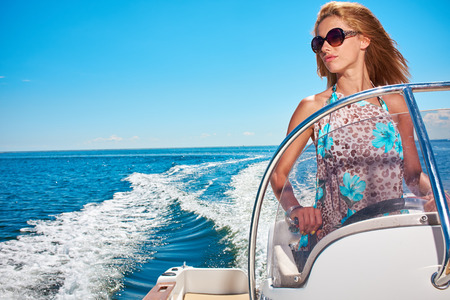power boat: Summer vacation - young woman driving a motor boat