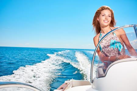 Summer vacation - young woman driving a motor boat Фото со стока - 37397546